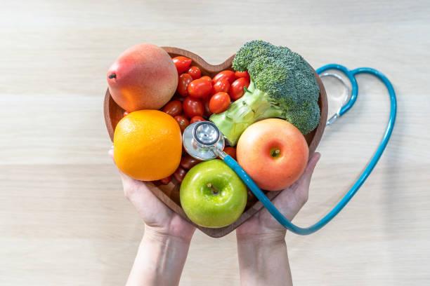 營養學家和醫生推薦營養品在心臟菜中吃乾淨的水果和蔬菜,以膽固醇飲食和健康營養飲食促進心臟健康,促進患者健康 - 健康飲食 個照片及圖片檔