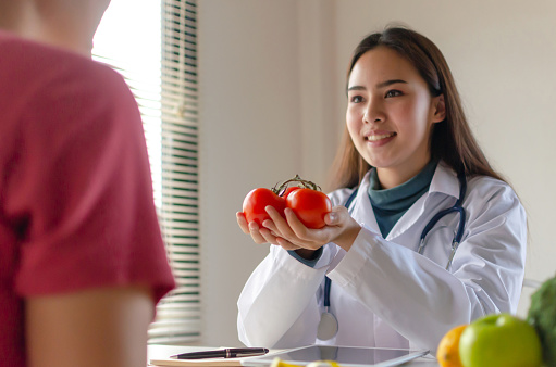 istock Nutritional. fresh tomato in hand of friendly nutritionist female doctor medical talking about diet plan young patient woman slim body in office hospital, nutrition, food science, healthy food concept 1215616228
