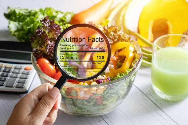 nutritional information concept. hand use the magnifying glass to zoom in to see the details of the nutrition facts from food , salad bowl nutritional information concept. hand use the magnifying glass to zoom in to see the details of the nutrition facts from food , salad bowl healthy eating stock pictures, royalty-free photos & images
