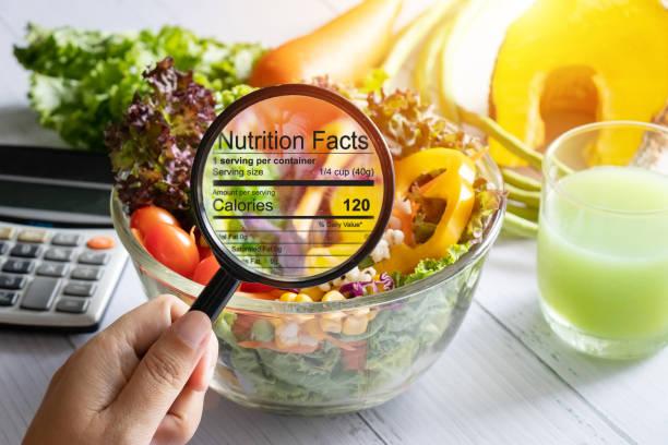 栄養情報の概念。手は、食品、サラダボウルからの栄養の事実の詳細を見るためにズームインに虫眼鏡を使用してください - food and drink ストックフォトと画像