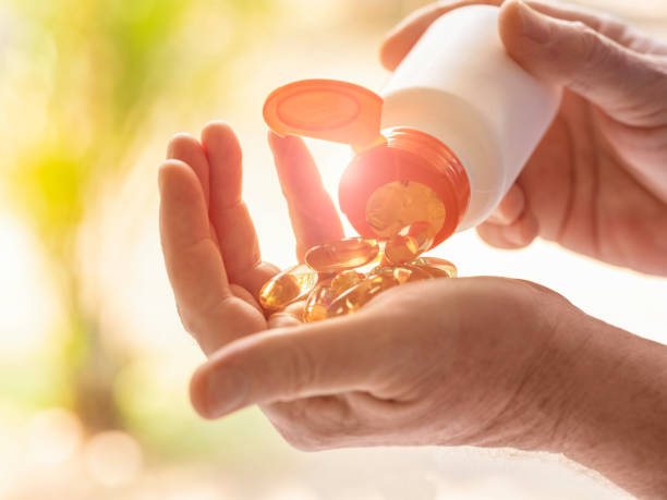 Nutritional supplement capsules being placed from a medicine bottle into the palm of a man's hand. stock photo