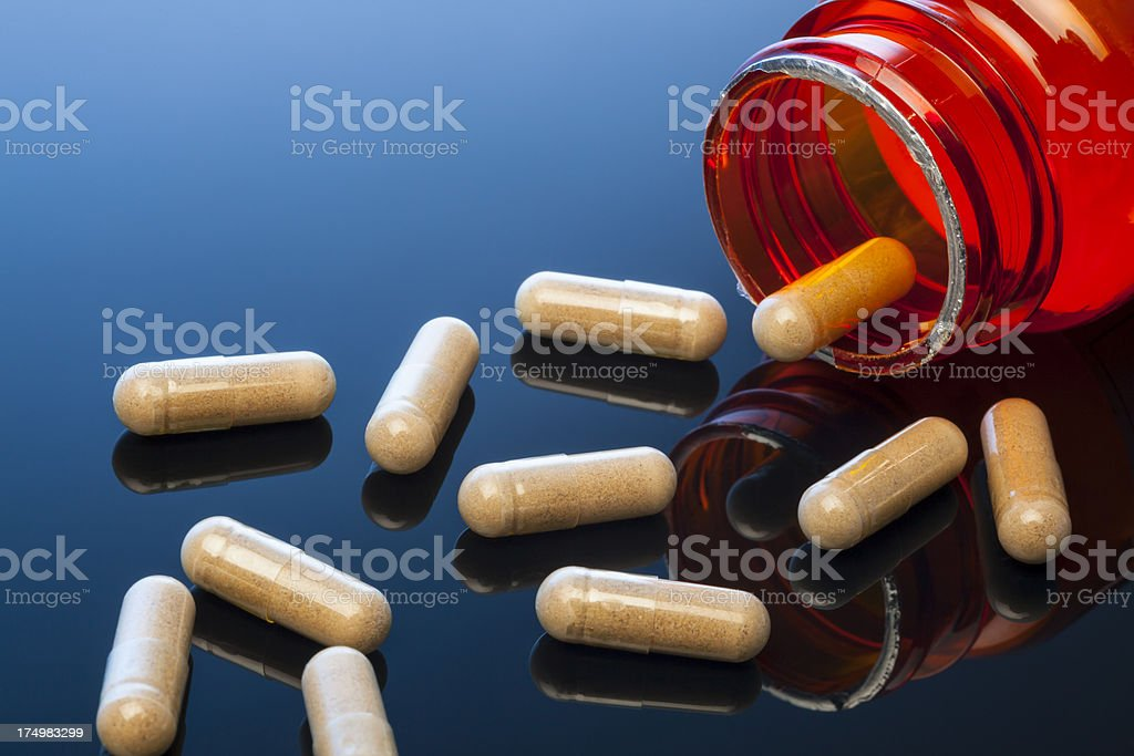 Nutritional Supplement Capsules on Reflective Surface royalty-free stock photo