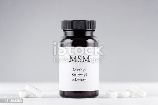 nutritional supplement msm, sulfur, methyl sulfonyl methan bottle and capsules on gray background