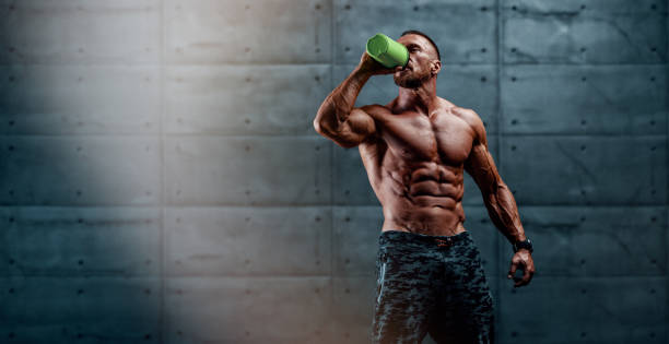 Nutritional Supplement. Muscular Men Drinks Protein, Energy Drink After Workout stock photo