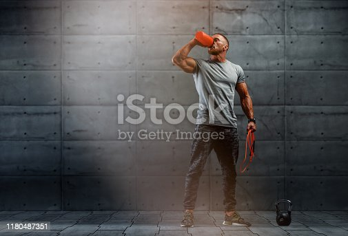 istock Nutritional Supplement. Muscular Men Drinks Protein, Energy Drink After Workout. Copy Space 1180487351