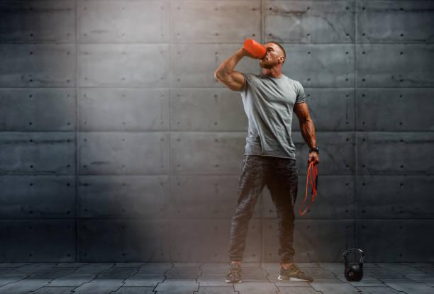 nahrungsergänzungsmittel. muskuläre männer trinkt protein, energy drink nach dem training. kopierraum - nahrungsergänzungsmittel stock-fotos und bilder