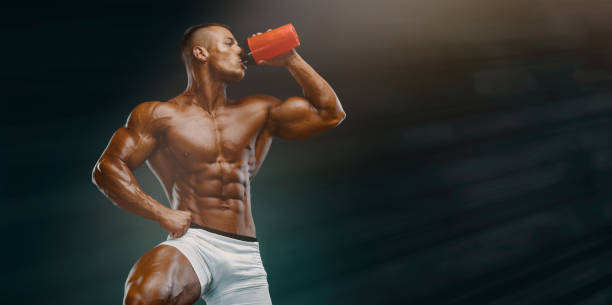 Nutritional Supplement. Muscular Men Drinks Protein, Energy Drink After Workout. Copy Space stock photo