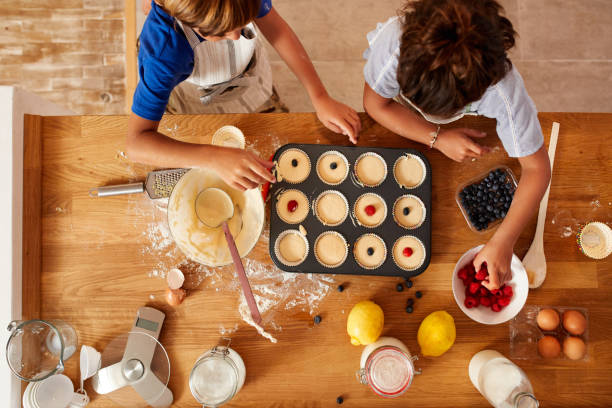 Nutritional to make parents happy and yummy for kids High angle shot of a brother and sister adding fruit to their batter before it gets baked in the oven at home muffin tin stock pictures, royalty-free photos & images