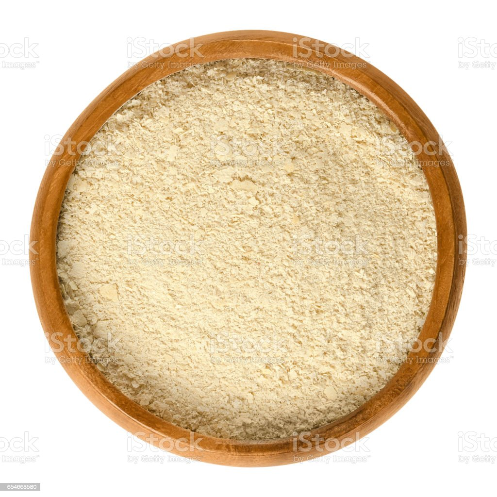 Nutritional yeast flakes in wooden bowl over white stock photo