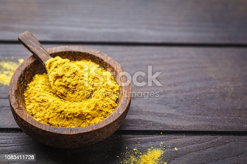 Nutritional yeast in a wooden bowl, copy space, dark background, copy space. Healthy vegan food concept.