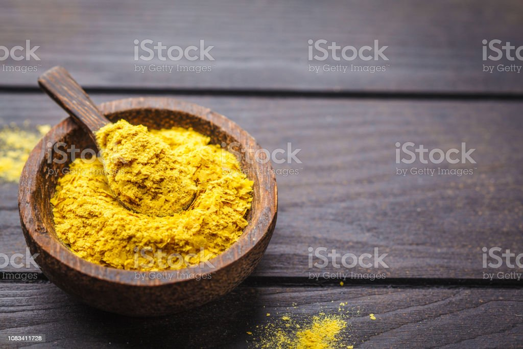 Nutritional yeast in a wooden bowl, copy space. Healthy vegan food concept. stock photo