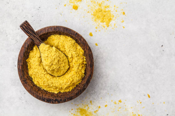 Nutritional yeast in a wooden bowl, copy space. Healthy vegan food concept. Nutritional yeast in a wooden bowl, copy space, white background, copy space. Healthy vegan food concept. yeast stock pictures, royalty-free photos & images