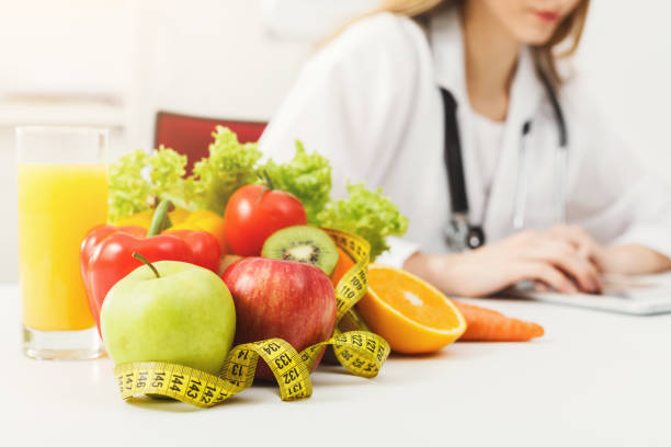 Nutritionist desk with fruit and measuring tape stock photo