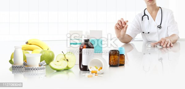 istock nutritionist doctor shows the pill in his hand at the desk office with apple, fruits, yogurt, tape meter and supplements drugs, healthy and balanced diet concept, web banner and copy space template 1127093045