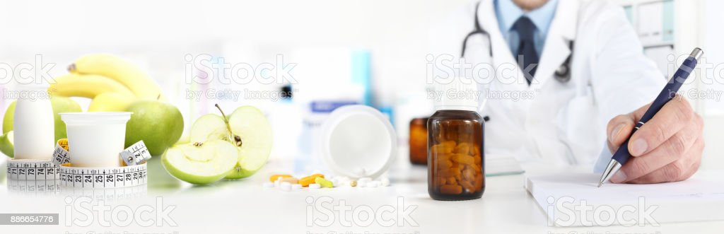 Nutritionist doctor writes the medical prescription for a correct diet on a desk with fruits, drugs and supplements, web banner and copy space template stock photo