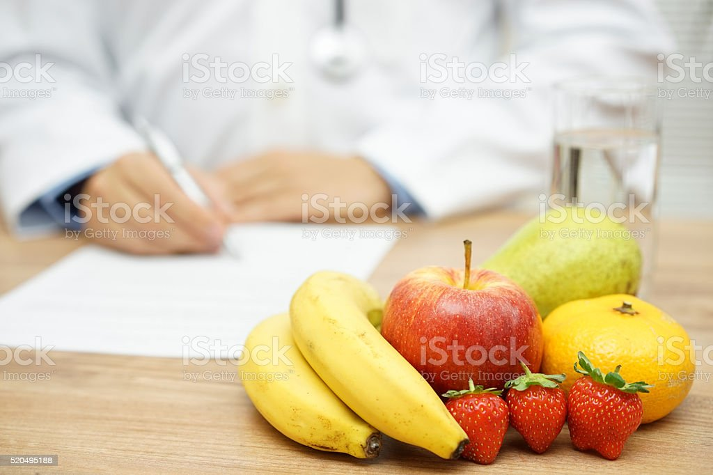Nutritionist Doctor writing diet plan, focus on fruit and water stock photo