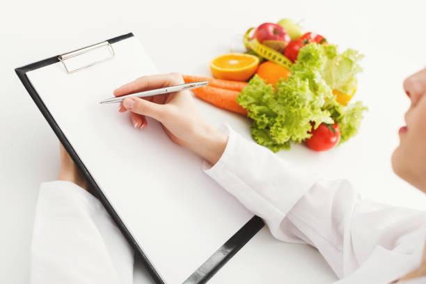 ernährungsberaterin arzt schreiben diätplan auf tisch - menüplanung vorlagen stock-fotos und bilder