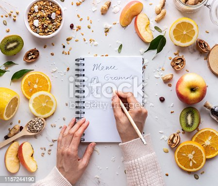 Nutritionist female hand write in notebook on healthy food background, women diet nutrition recipe menu, fresh summer fruit granola seeds on white table organic super food health care detox, top view