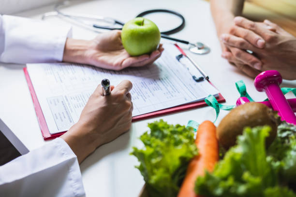 nutritionist giving consultation to patient with healthy fruit and vegetable, right nutrition and diet concept - dietician stock pictures, royalty-free photos & images