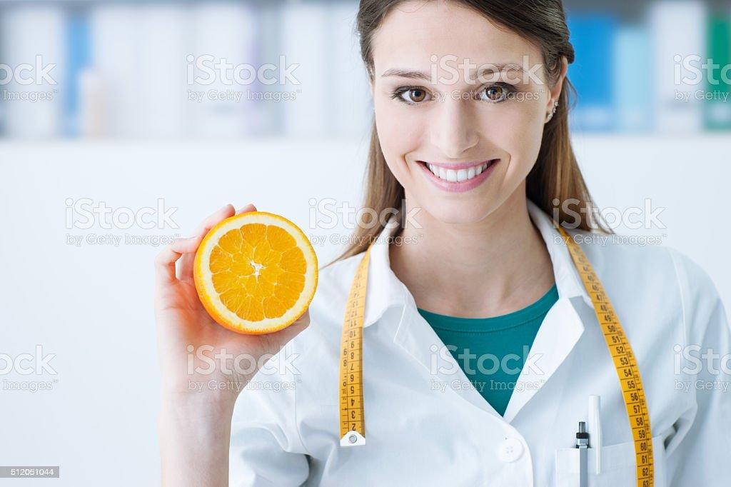 Nutritionist holding a sliced orange stock photo