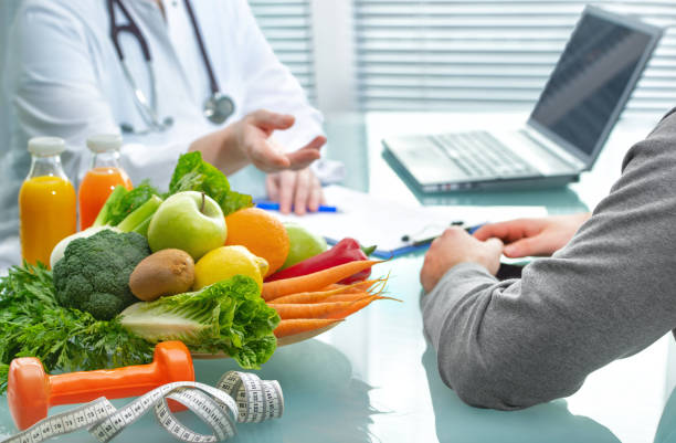 Nutritionist is consulting the patient about healthy diet with vegetables and fruits stock photo