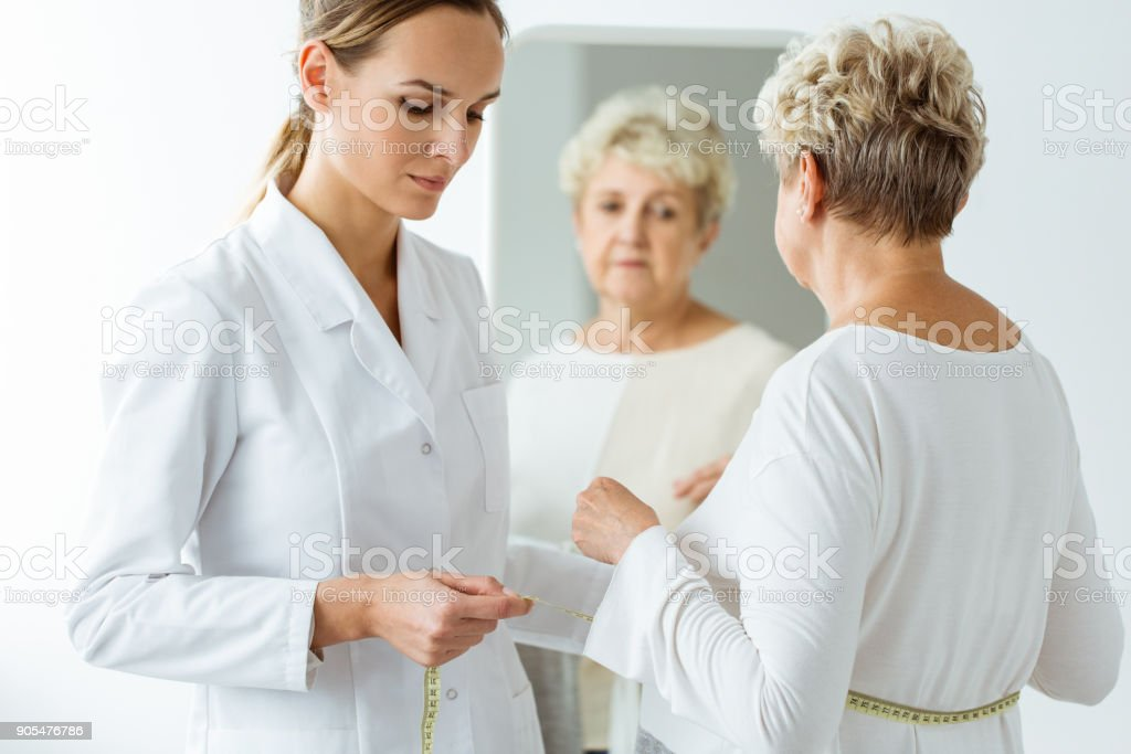 Nutritionist measuring patient's body circumference stock photo