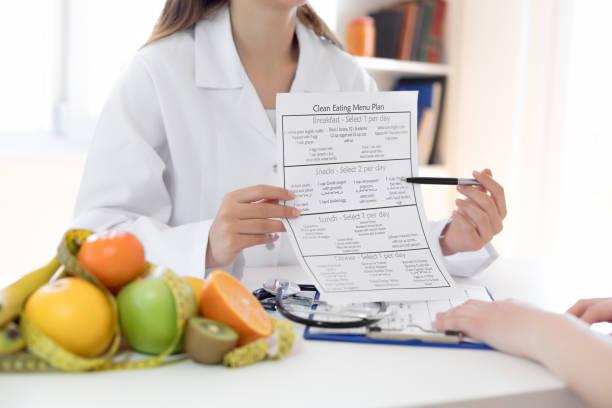 ernährungswissenschaftler zeigt ernährungsplan - ernährungsberater stock-fotos und bilder