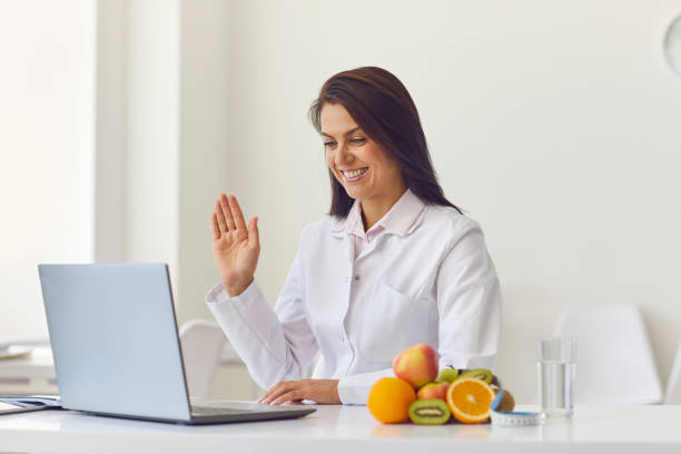 Nutritionist uses a laptop to conduct an online consultation with his patient. stock photo