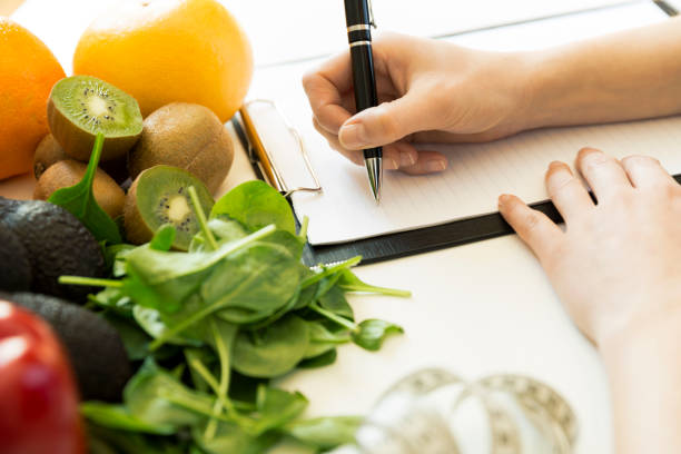 Nutritionist woman writing diet plan on table full of fruits and vegetables stock photo