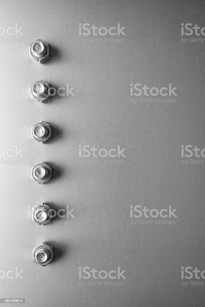Nuts and bolts in a row on sheet metal stock photo