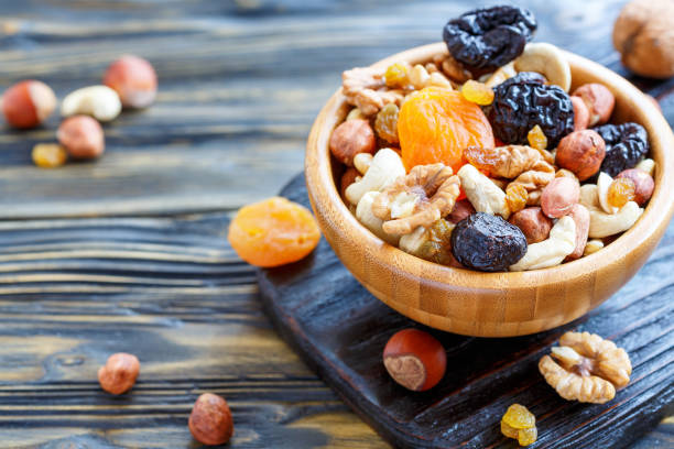 nuts and dried fruit in a wooden bowl. - dried fruit stock photos and pictures