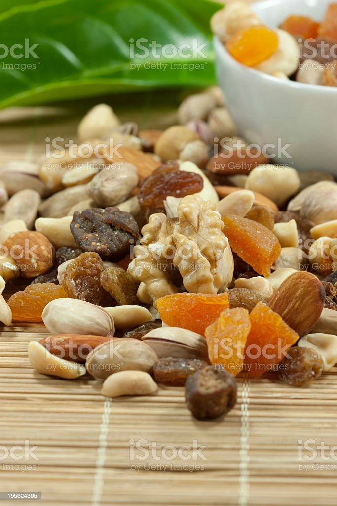 Nuts and dried fruits on a bamboo place mat royalty-free stock photo