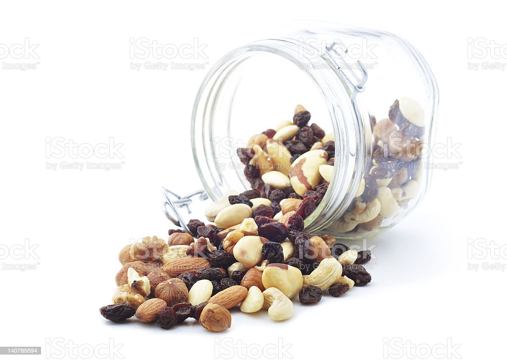 Nuts and dried fruits spilled from a jar stock photo