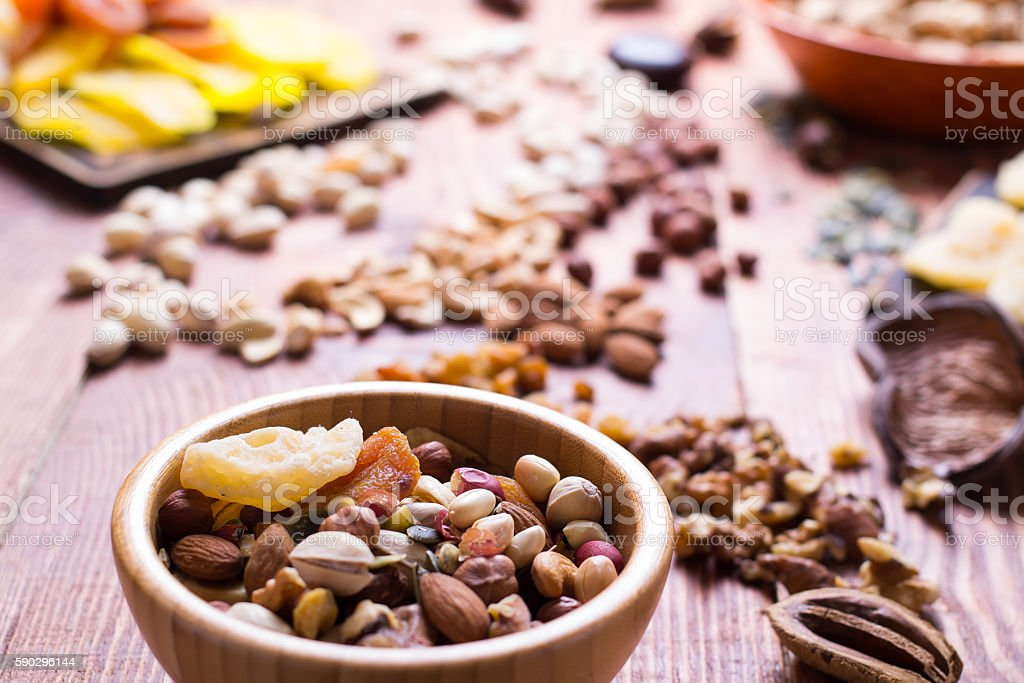 Nuts and dry fruit, in bowls, on boards Стоковые фото Стоковая фотография
