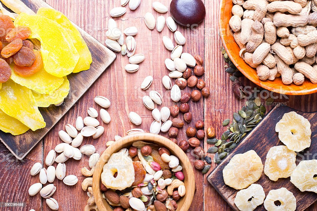 Nuts and dry fruit, in bowls, on boards royaltyfri bildbanksbilder
