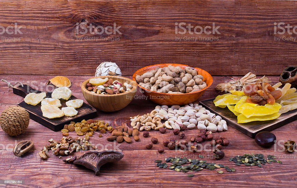 Nuts and dry fruit, in plates, on boards Стоковые фото Стоковая фотография
