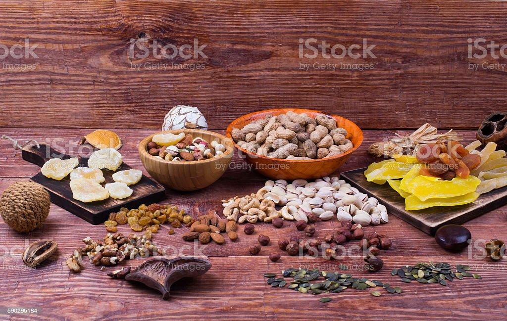 Nuts and dry fruit, in plates, on boards royaltyfri bildbanksbilder