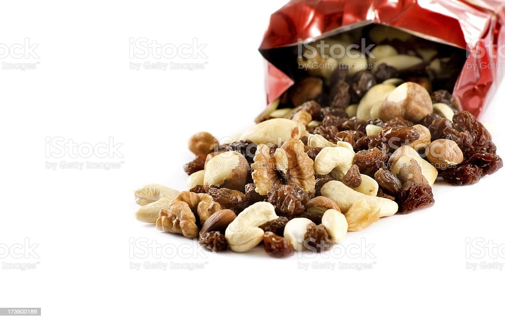 nuts and raisins falling out of the red bag, isolated royalty-free stock photo