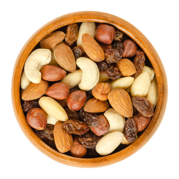 Nuts and raisins in wooden bowl over white stock photo