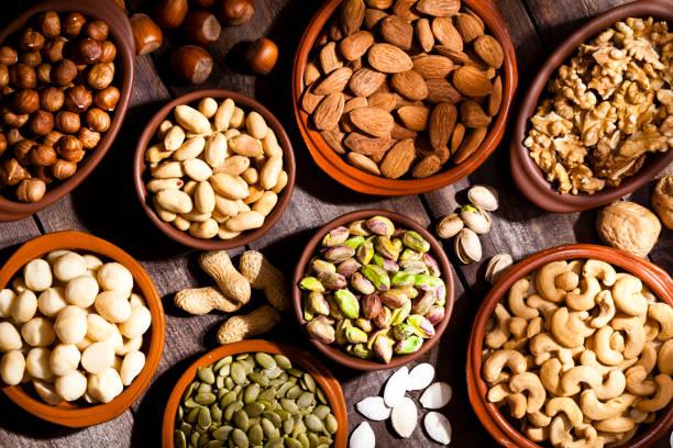 nuts assortment on rustic wood table. - frutos secos imagens e fotografias de stock