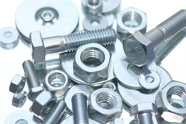 Nuts, bolts and washers Closeup of steel nuts and bolts, Blue tone, Shallow focus. washer fastener stock pictures, royalty-free photos & images