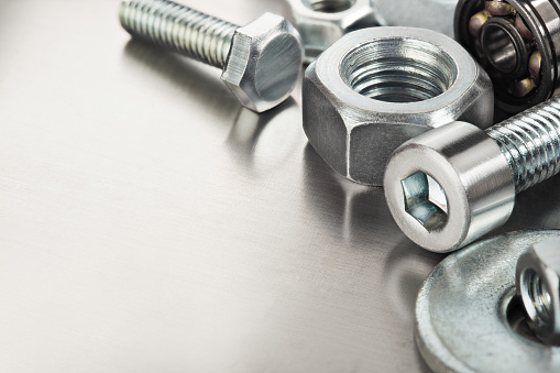 nuts, bolts, screws, washers, bearings on a metal steel background.