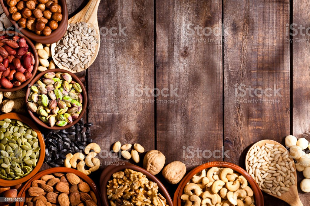 Nuts border on on rustic wood table stock photo