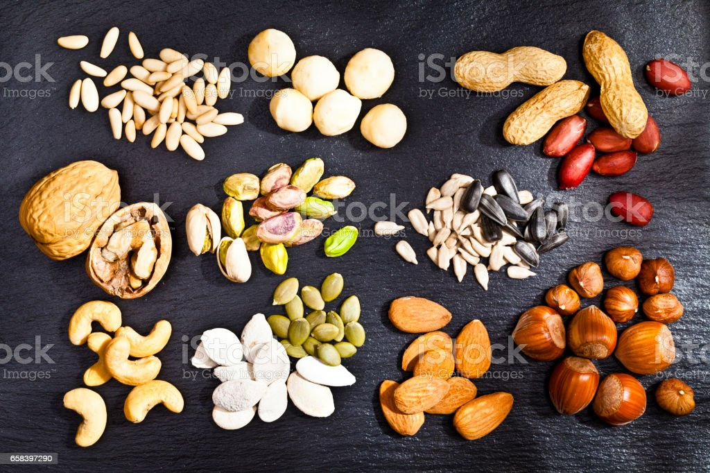 Nuts collection on dark slate background stock photo