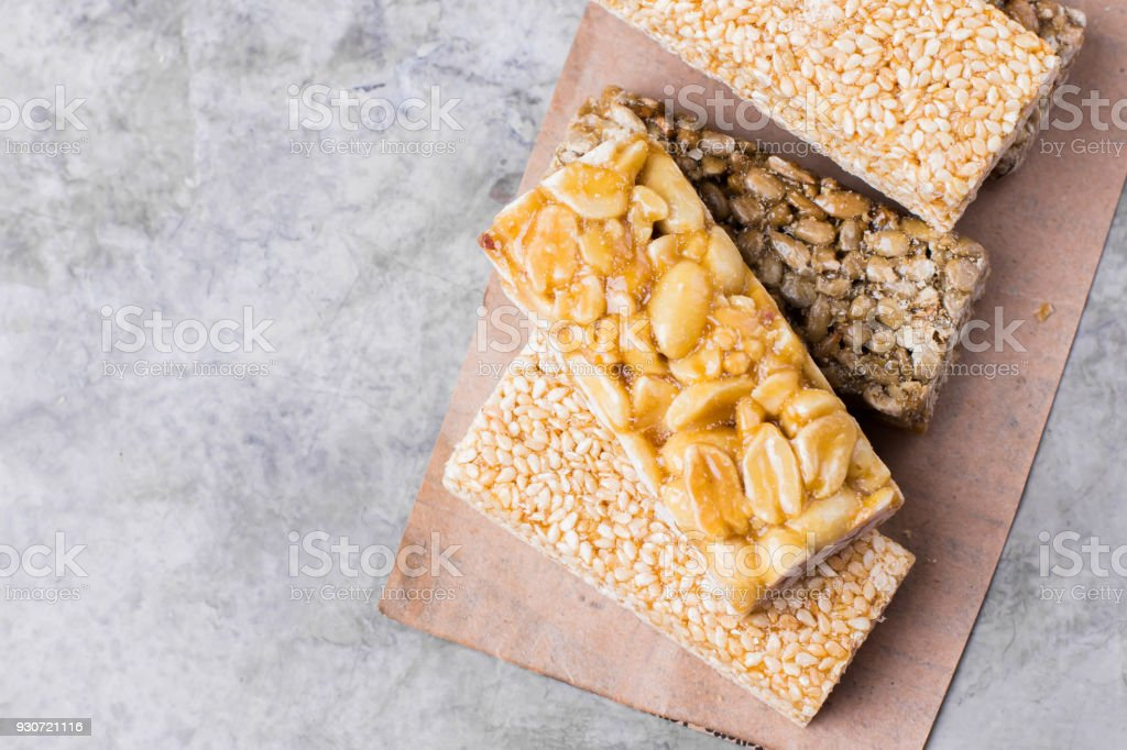 Nuts in caramel, honey on gray table background. Snack food. Uhealthy eating. Copy space stock photo