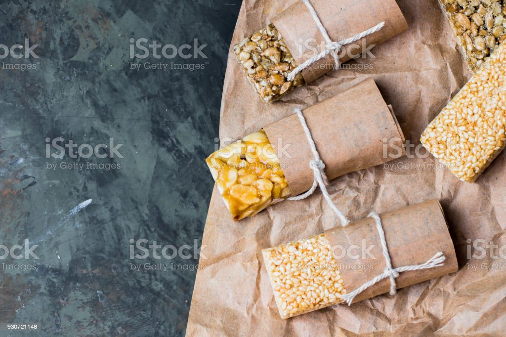 Nuts in caramel, honey on green stone table background. Snack food. Uhealthy eating. Copy space, top view stock photo
