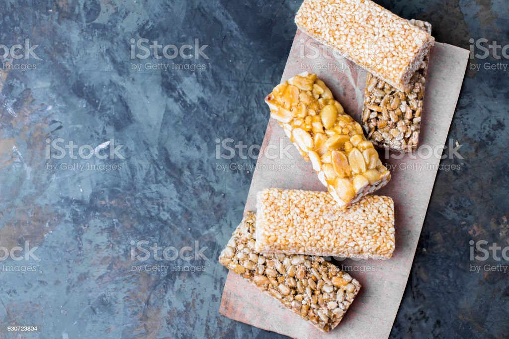 Nuts in caramel, honey on green stone table background. Snack food. Uhealthy eating. Copy space stock photo