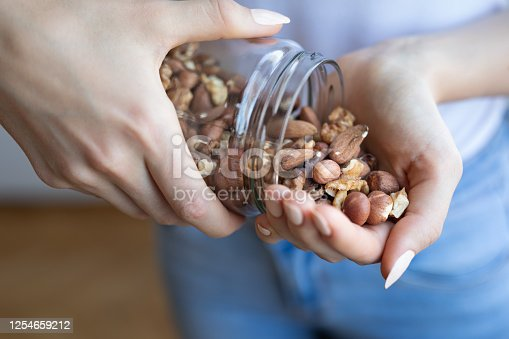 istock Nuts in woman hands 1254659212