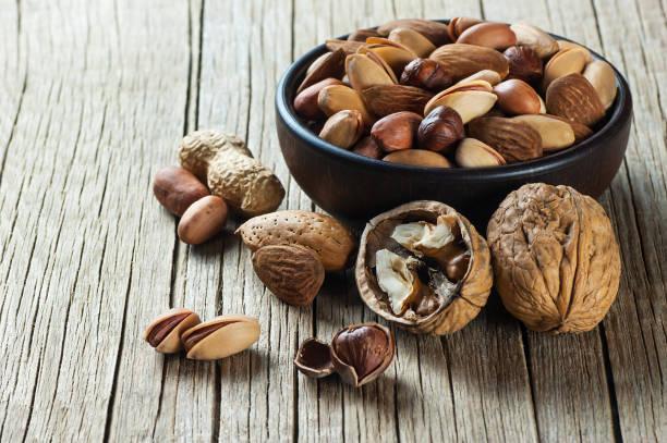 ナッツ ミックス ドライ フルーツ、ナットの種類、木製のテーブルの健康食品。クルミ、ヘーゼル ナッツ、ピスタチオ、ピーナッツ、アーモンド。ナッツの盛り合わせコンセプト - ナッツ類 ストックフォトと画像