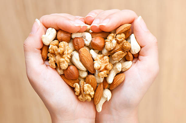 Nuts' mixture Various nuts in woman hands  forming heart shape handful stock pictures, royalty-free photos & images